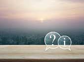 Question mark and information chat icon on wooden table over cityscape at sunset, vintage style, Customer support concept
