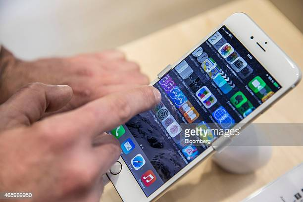 A customer swipes app icons on an Apple Inc iPhone 6 smartphone screen inside a Orange SA mobile phone store in Marseille France on Thursday March 12...