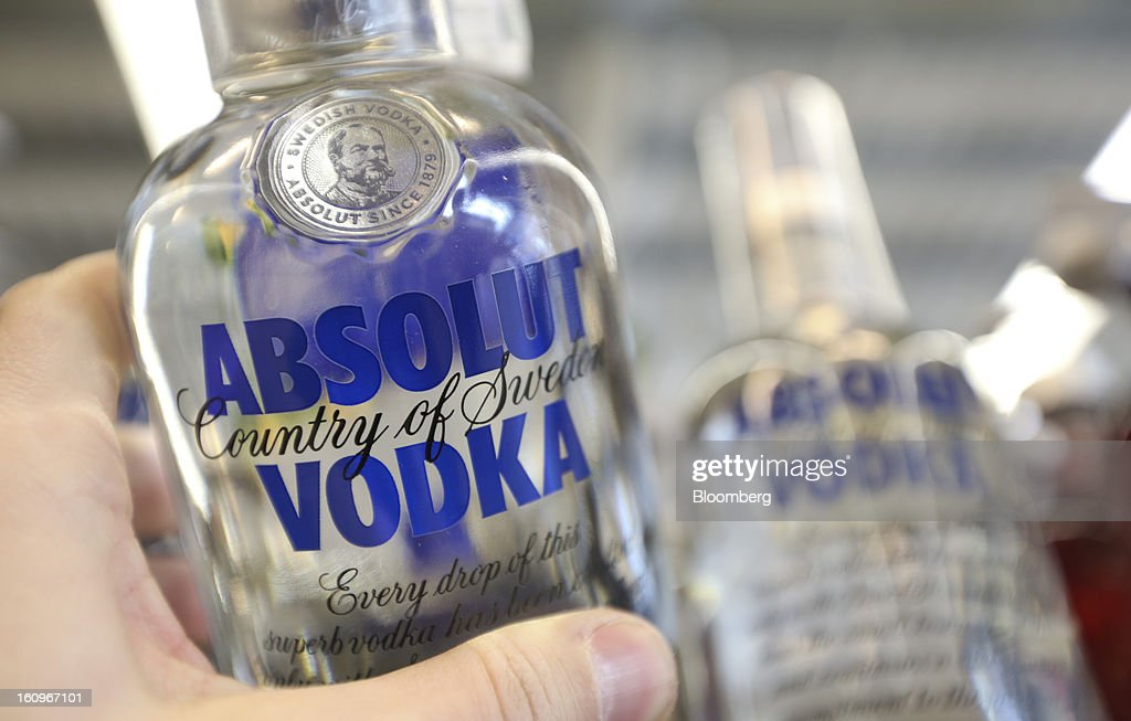 A customer takes a bottle of Absolut vodka, produced by Pernod Ricard SA, from a shelf inside a supermarket in London, U.K., on Friday, Feb. 8, 2013. Britain's economy will grow more slowly this year than previously forecast and stagnation may persist, according to the National Institute of Economic and Social Research. Photographer: Chris Ratcliffe/Bloomberg via Getty Images
