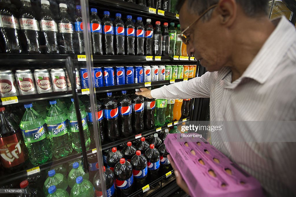 A customer takes a bottle of PepsiCo Inc. soft drink from a display at a store in Mexico City, Mexico, on Monday, July 22, 2013. PepsiCo Inc. is expected to release earnings data on July 24. Photographer: Susana Gonzalez/Bloomberg via Getty Images