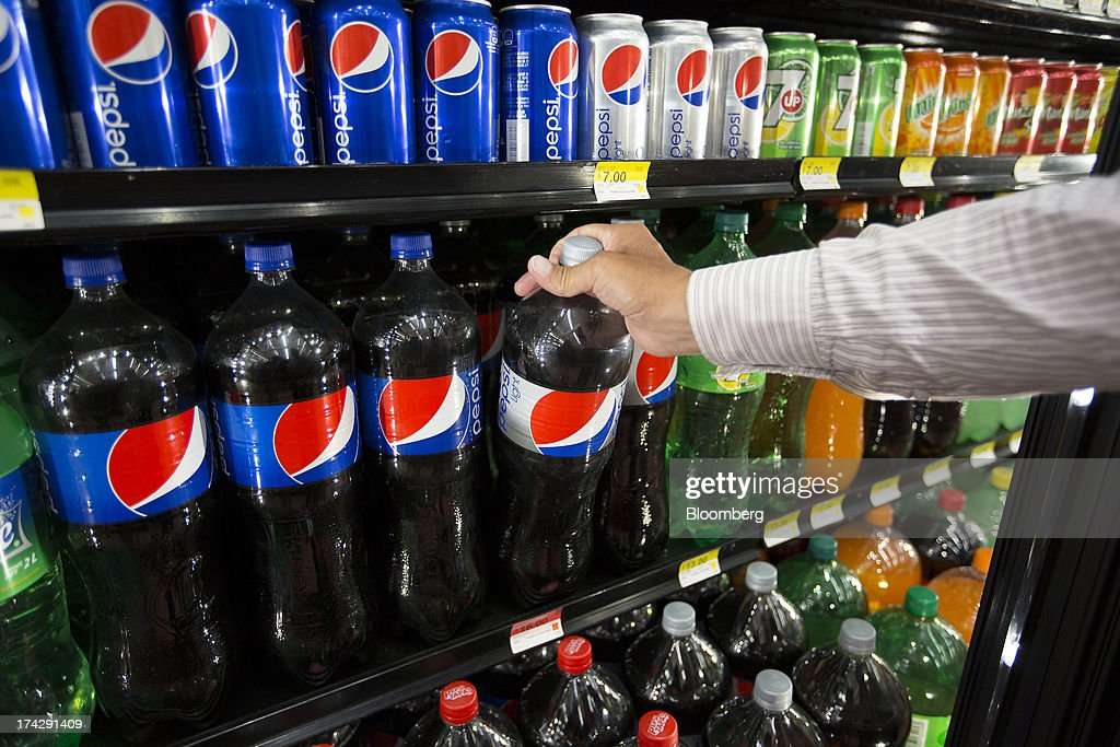 A customer takes a bottle of PepsiCo Inc. soft drink from a fridge at a store in Mexico City, Mexico, on Monday, July 22, 2013. PepsiCo Inc. is expected to release earnings data on July 24. Photographer: Susana Gonzalez/Bloomberg via Getty Images