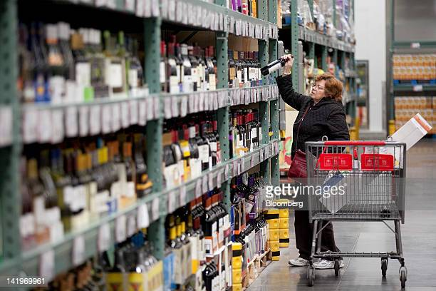 A customer takes a bottle of wine off a shelf at a BJ's Wholesale Club Inc store in Falls Church Virginia US on Tuesday March 27 2012 The US Bureau...