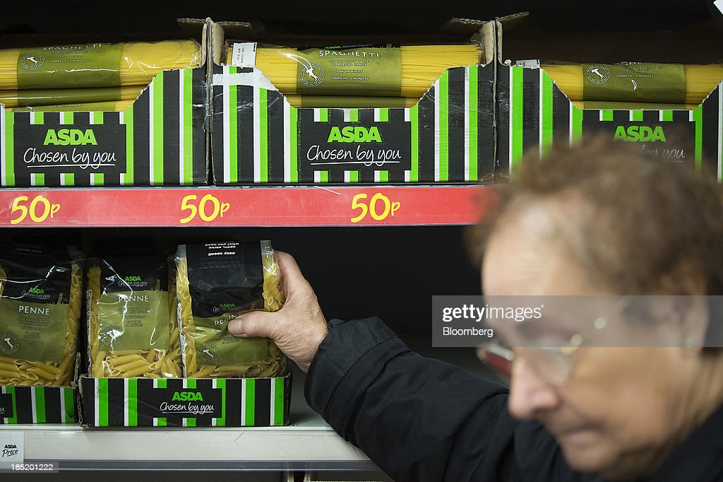 A customer takes a packet of pasta from a display shelf inside an Asda supermarket, the U.K. retail arm of Wal-Mart Stores Inc., in Watford, U.K., on Thursday, Oct. 17, 2013. U.K. retail sales rose more than economists forecast in September as an increase in furniture demand led a rebound from a slump the previous month. Photographer: Simon Dawson/Bloomberg via Getty Images