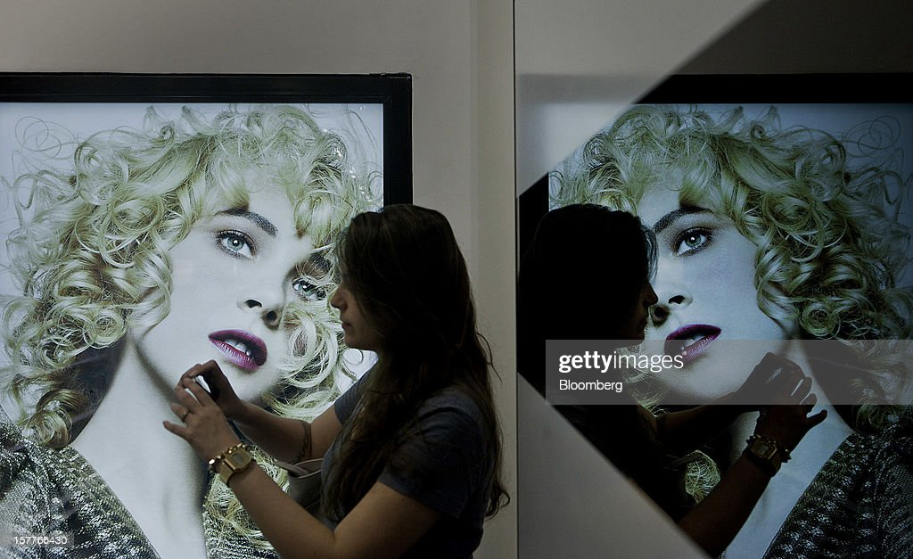 A customer takes a photo while standing next to an advertisement during the opening of a Sephora SA store at the Riosul shopping mall in Rio de Janeiro, Brazil, on Wednesday, Dec. 5, 2012. Sephora SA, a French beauty product retail chain, opened its first Brazil location earlier this year in July. Photographer: Dado Galdieri/Bloomberg via Getty Images