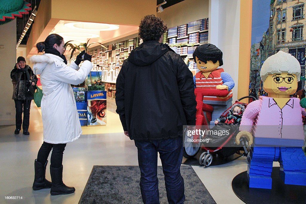 A customer takes a photograph of a giant models built from building blocks on her mobile phone inside a Lego A/S toy store in Copenhagen, Denmark, on Friday, Jan. 11, 2013. The 'Lego Friends' series, introduced in January in most markets, is Lego's sixth attempt over the years to target girls and the 'most significant' new product in a decade, according to Chief Executive Officer Joergen Vig Knudstorp. Photographer: Freya Ingrid Morales/Bloomberg via Getty Images