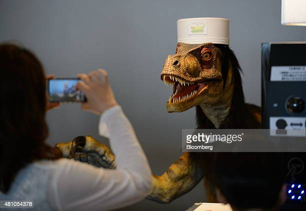 A customer takes a photograph of a Kokoro Company Ltd humanoid robot right at the reception desk of Henn na Hotel operated by Huis Ten Bosch Co a...