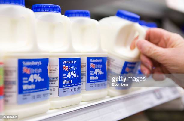 A customer takes a pint of milk from the shelf at a Sainsbury's supermarket in Chafford Hundred UK on Wednesday May 13 2010 The UK's third largest...