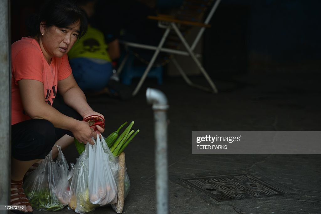 A customer takes a rest in a market in Shanghai on July 15, 2013. China's gross domestic product expanded 7.5 percent in the April-June quarter, official data showed, a second consecutive slowdown in growth as worries mount over the health of the world's number two economy. AFP PHOTO/Peter PARKS