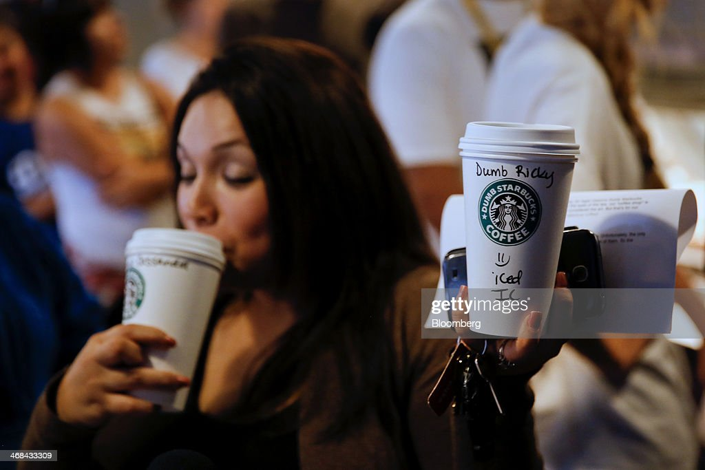A customer takes a sip of coffee while holding up a cup during a television interview at the Dumb Starbucks Coffee store, a parody of the Starbucks Corp. coffee chain, in Los Angeles, California, U.S., on Monday, Feb. 10, 2014. Dumb Starbucks, which opened this past weekend, offered Dumb Vanilla Blonde Roast, Dumb Chai Tea Latte, and Dumb Caramel Macchiato, all available in sizes Dumb Venti, Dumb Grande, and Dumb Tall. Photographer: Patrick T. Fallon/Bloomberg via Getty Images