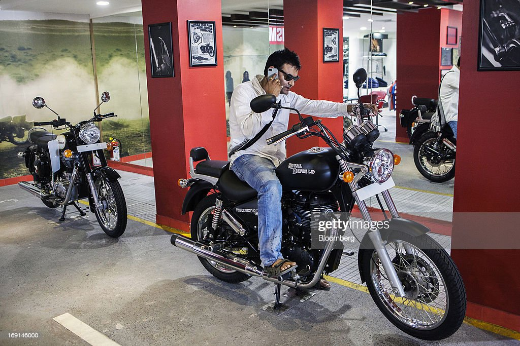 A customer talks on his mobile phone as he sits on an Eicher Motors Ltd. Royal Enfield Thunderbird 500 motorcycle on display at the company's Royal Enfield flagship dealership in Gurgaon, India, on Monday, May 20, 2013. The Indian maker of Royal Enfield, the World War II-era British motorcycle owned by stars including Brad Pitt, plans to export the vehicles to Southeast Asia and Latin America as it builds on record sales at home. Photographer: Prashanth Vishwanathan/Bloomberg via Getty Images