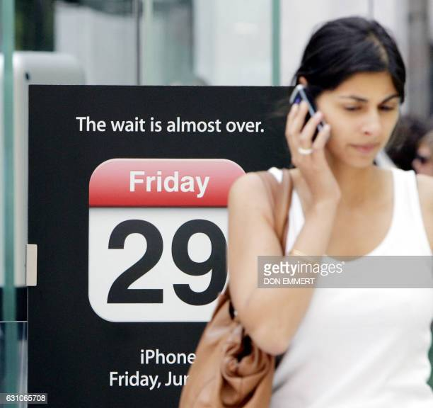 A customer talks on the phone as she walk past a sign announcing the iPhone at the Apple store in New York 26 June 2007 The 29 June release of...