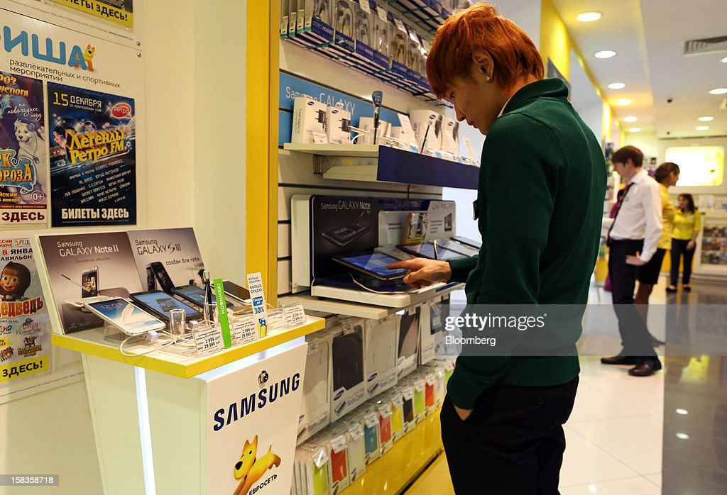 A customer tests a Samsung Electronics Co. Galaxy tablet inside a Euroset Holding NV mobile phone store in Moscow, Russia, on Thursday, Dec. 13, 2012. OAO MegaFon and its main shareholder billionaire Alisher Usmanov bought 50 percent of Euroset Holding NV in a deal that gives Russia's biggest handset retailer an enterprise value of $2.3 billion. Photographer: Andrey Rudakov/Bloomberg via Getty Images