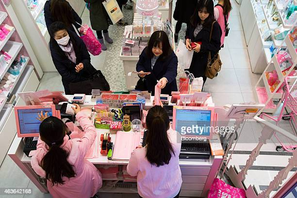 A customer top center pays for her purchase at the checkout counter of an Amorepacific Corp Etude House store in the Myeongdong shopping district in...
