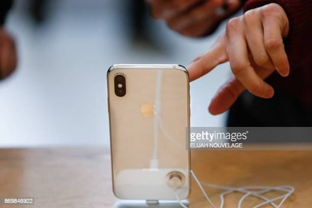 A customer touches the screen of the new iPhone X at the Apple Store Union Square on November 3 in San Francisco California Apple's flagship iPhone X...