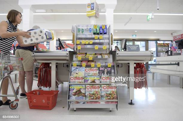A customer transfers items from a shopping cart to a checkout counter at a Coles supermarket operated by Wesfarmers Ltd in the Richmond area of...