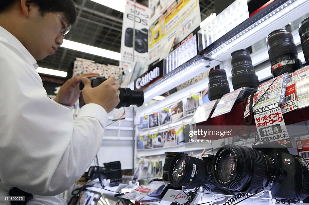 A customer tries a Canon Inc. digital camera at an electronics store in Tokyo, Japan, on Tuesday, July 23, 2013. Canon Inc., the world's largest camera maker, is scheduled to release earnings on July 24. Photographer: Tomohiro Ohsumi/Bloomberg via Getty Images