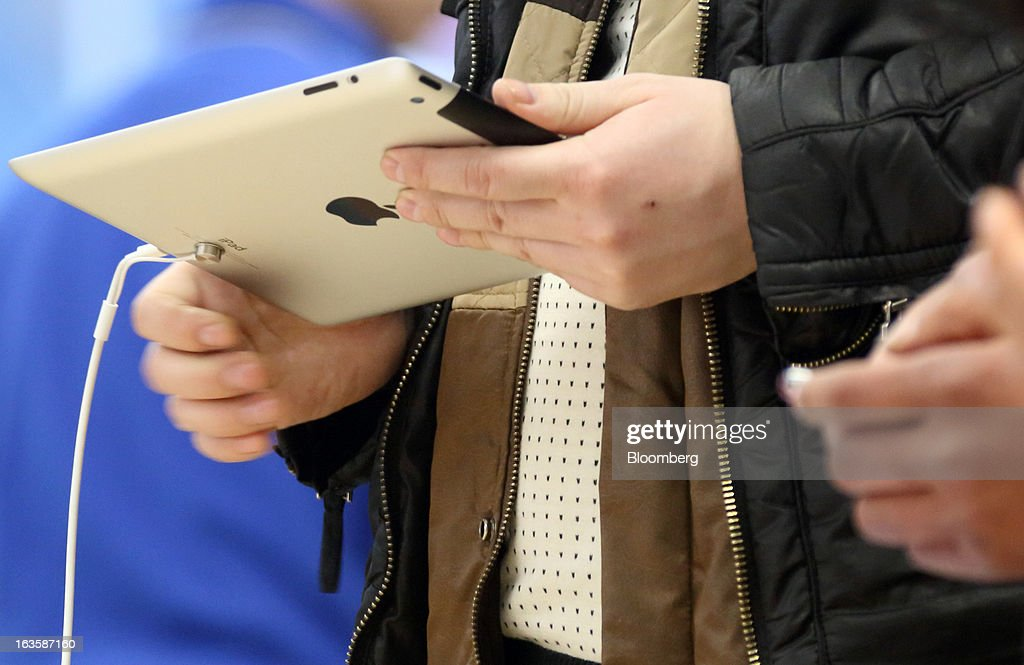 A customer tries an Apple Inc. iPad at the company's store in the Wangfujing area of Beijing, China, on Tuesday, March 12, 2013. Apple's Wangfujing store is the largest in Asia. Photographer: Tomohiro Ohsumi/Bloomberg via Getty Images