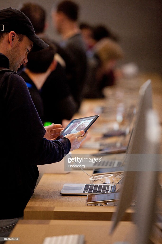 A customer tries an Apple Inc. iPad on display at the new Apple Inc. store located on Kurfurstendamm Street in Berlin, Germany, on Friday, May 3, 2013. Apple Inc.'s latest showcase store, their first in the German capital city will open its doors to the public today. Photographer: Krisztian Bocsi/Bloomberg via Getty Images