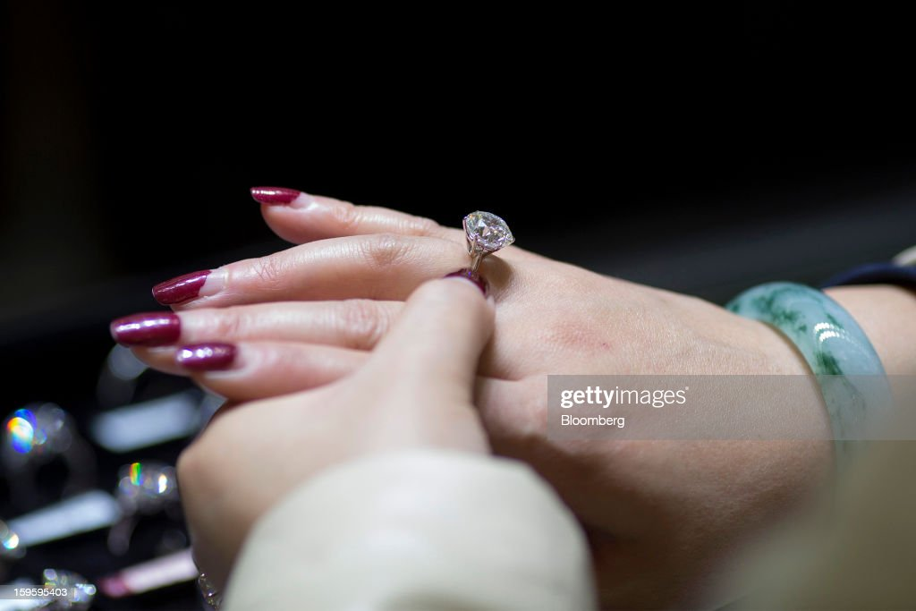 A customer tries on a diamond ring in a Chow Tai Fook Jewellery Group Ltd. store in the Central district of Hong Kong, China, on Wednesday, Jan. 16, 2013. Chow Tai Fook Jewellery, the world's biggest jeweler by market value, posted an 8 percent drop in third-quarter same-store sales as Chinese shoppers curbed spending amid a slower economy. Photographer: Jerome Favre/Bloomberg via Getty Images