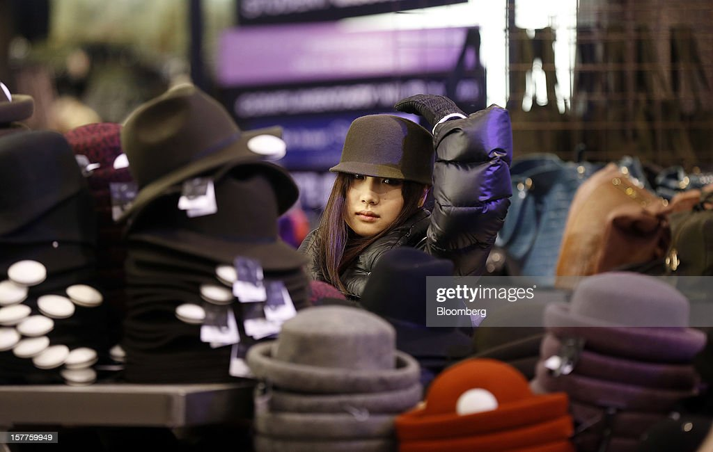 A customer tries on a hat in the womenswear department of a Topshop store, owned by Arcadia Group Ltd., on Oxford Street in London, U.K., on Thursday, Dec. 6, 2012. Philip Green, the billionaire owner of the Arcadia fashion business, sold a 25 percent stake in the Topshop and Topman retail chains to Leonard Green & Partners LP, the co-owner of the J Crew fashion brand, in a deal valuing the businesses at 2 billion pounds ($3.2 billion). Photographer: Simon Dawson/Bloomberg via Getty Images