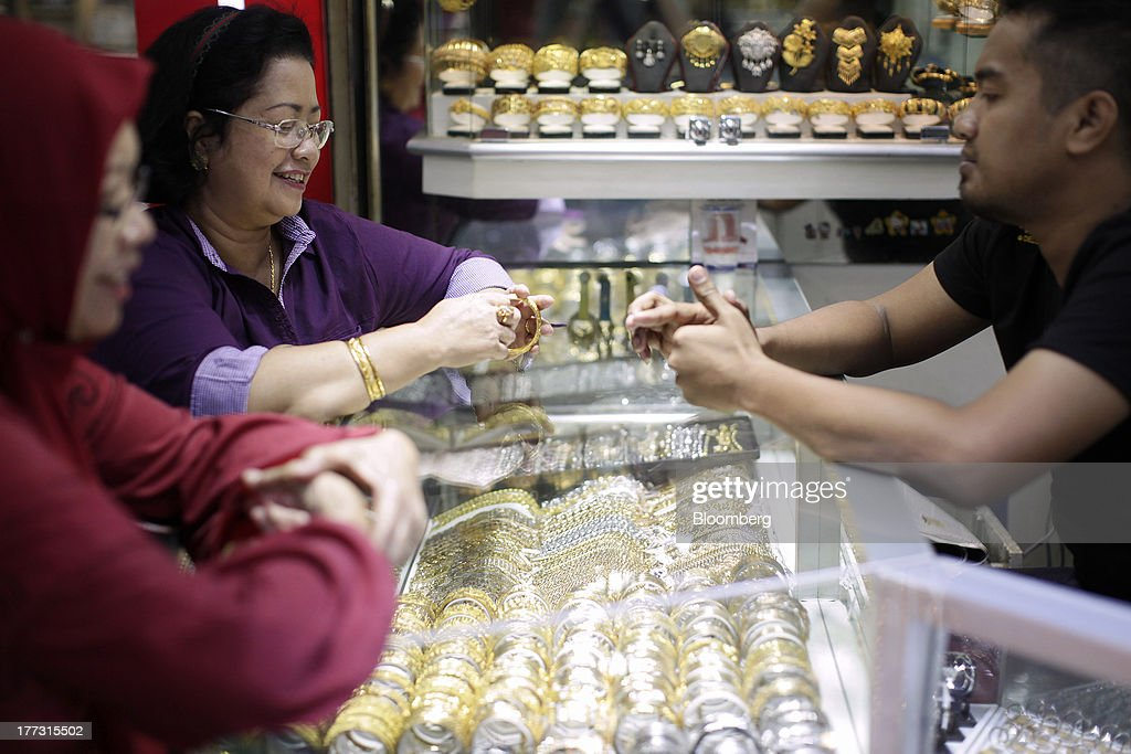A customer tries on gold bracelets at a jewelry store in Jakarta, Indonesia, on Thursday, Aug. 22, 2013. Gold jewelry demand in Indonesia is set to expand to a four-year high as consumers in Southeast Asia's biggest buyer join India to China in increasing purchases as prices slump and the middle class expands. Photographer: Dimas Ardian/Bloomberg via Getty Images