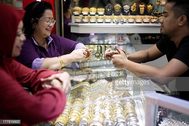 A customer tries on gold bracelets at a jewelry store in Jakarta Indonesia on Thursday Aug 22 2013 Gold jewelry demand in Indonesia is set to expand...
