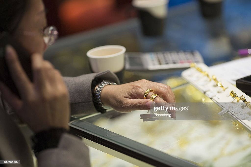 A customer tries on rings while using a mobile phone in a Chow Tai Fook Jewellery Group Ltd. store in the Central district of Hong Kong, China, on Wednesday, Jan. 16, 2013. Chow Tai Fook Jewellery, the world's biggest jeweler by market value, posted an 8 percent drop in third-quarter same-store sales as Chinese shoppers curbed spending amid a slower economy. Photographer: Jerome Favre/Bloomberg via Getty Images