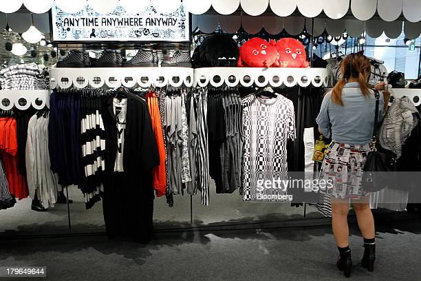 A customer tries out a bag at a Monki fashion store operated by Hennes Mauritz AB at the Cute Cube Harajuku commercial complex in the shopping...