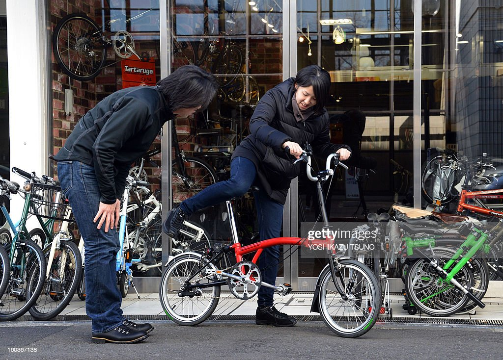 A customer (R) tries out a Brompton folding bicycle at a retail outlet in Yokohama, in Japan, on January 27, 2013. British bicycle company Brompton produced 36,000 bikes in 2012 with a turnover of around GBP 20m (approx 23.25m euros). Brompton's folding bikes have proved popular with customers in Asian countries such as Japan. AFP PHOTO / Yoshikazu TSUNO
