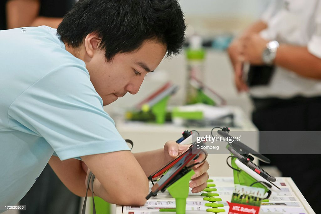 A customer tries out a HTC Corp. Butterfly S smartphone at one of the company's stores in Taipei, Taiwan, on Thursday, July 4, 2013. HTC is scheduled to announce second quarter earnings on July 8. Photographer: Maurice Tsai/Bloomberg via Getty Images