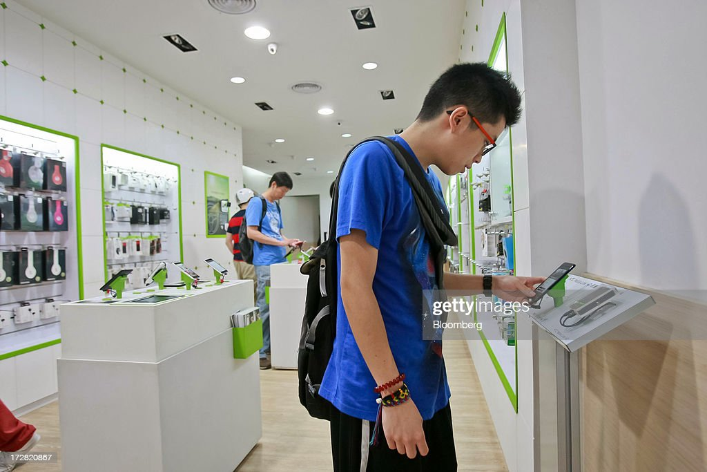 A customer tries out a HTC Corp. One smartphone at one of the company's stores in Taipei, Taiwan, on Thursday, July 4, 2013. HTC is scheduled to announce second quarter earnings on July 8. Photographer: Maurice Tsai/Bloomberg via Getty Images