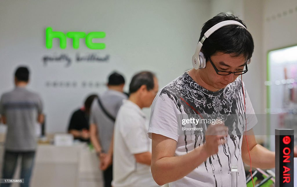 A customer tries out a HTC Corp. One X+ smartphone with a pair of Beats Electronics LLC headphones at one of the company's stores in Taipei, Taiwan, on Thursday, July 4, 2013. HTC is scheduled to announce second quarter earnings on July 8. Photographer: Maurice Tsai/Bloomberg via Getty Images