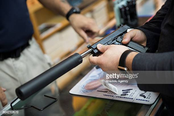 A customer tries out a Remington 1911 equipped with a silencer at Blue Ridge Arsenal in Chantilly Va USA on January 9 2015