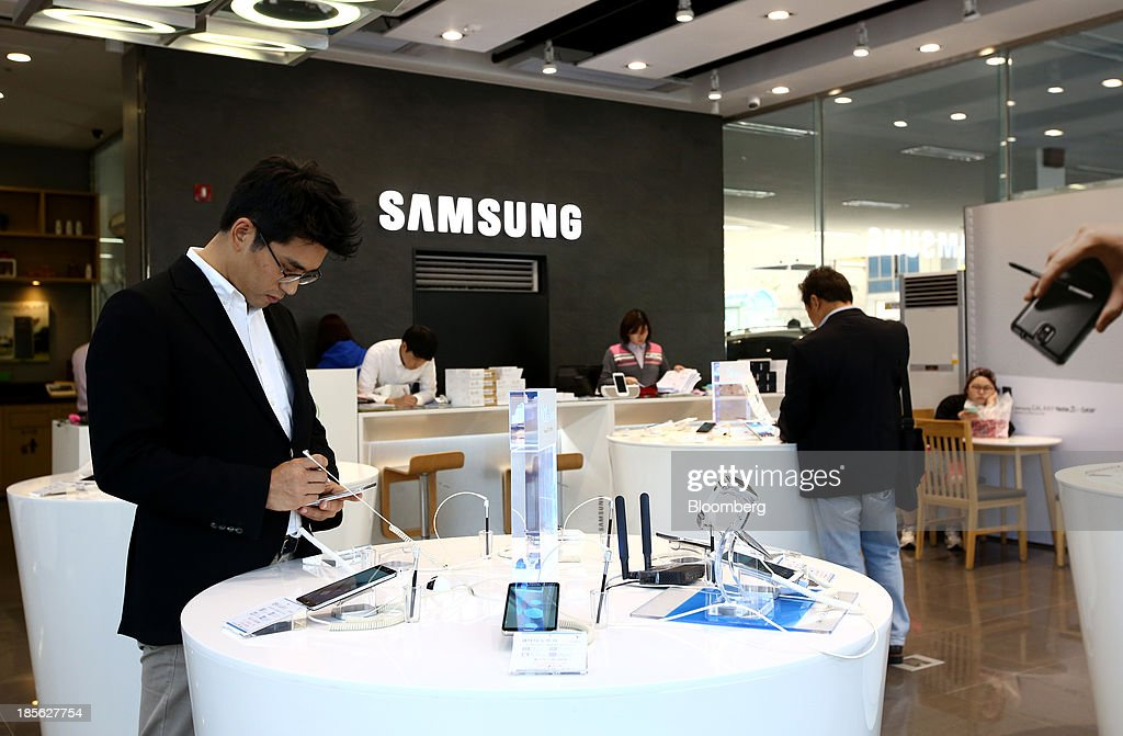 A customer tries out a Samsung Electronics Co. Galaxy Note 2 smartphone at the company's digital plaza store in the Gangnam district in Seoul, South Korea, on Tuesday, Oct. 22, 2013. Samsung Electronics is scheduled to release third-quarter earnings on Oct. 25. Photographer: SeongJoon Cho/Bloomberg via Getty Images
