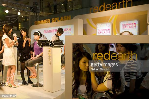 A customer tries out new cosmetics while a public makeup demonstration takes place in the background in Joy City the newest shopping mall to open in...