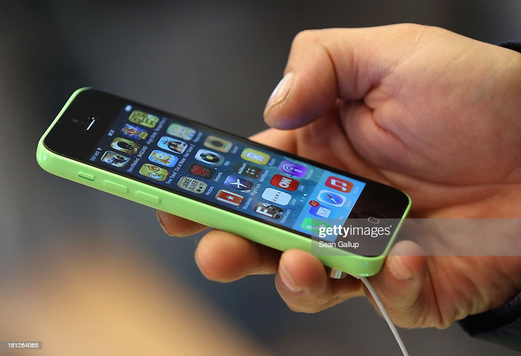 A customer tries out the new Apple iPhone 5C smartphone at the Berlin Apple Store on the first day of sales on September 20, 2013 in Berlin, Germany. The new iPhone 5S and 5C phones went on sale all over the world today and hundreds of customers waited outside the Berlin store in the rain to be among the first to buy the new phones starting at 8am.