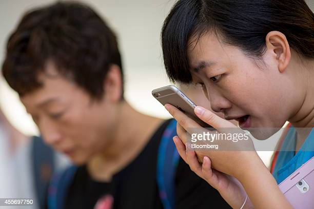 A customer tries the Siri voice recognition function on an Apple Inc iPhone 6 Plus at the company's Causeway Bay store during the sales launch of the...