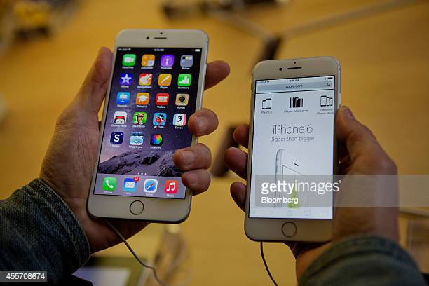 A customer tries to decide between an iPhone 6 Plus left and iPhone 6 during the sales launch at the Apple Inc store in New York US on Friday Sept 19...