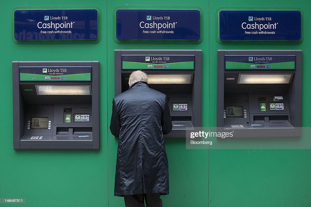 A customer uses a automated teller machine (ATM) outside a Lloyds TSB bank branch, part of the Lloyds Banking Group Plc, in London, U.K., on Wednesday, July 18, 2012. The U.K. financial regulator said it's investigating seven lenders over attempts to manipulate interbank offered rates as lawmakers criticized it for not opening the probe earlier. Photographer: Simon Dawson/Bloomberg via Getty Images