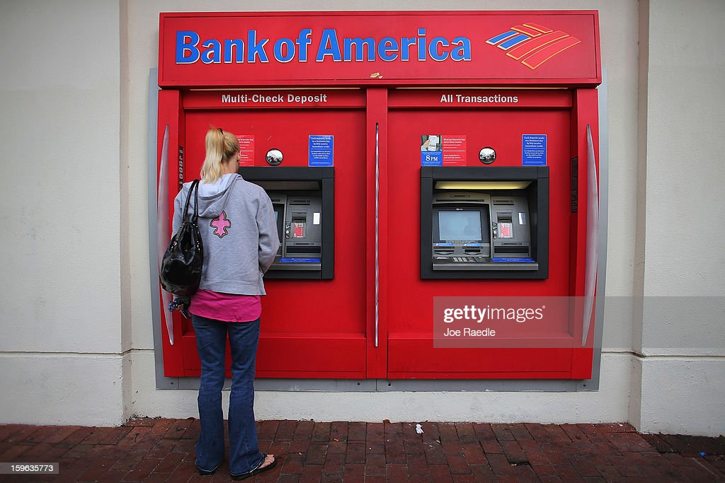 A customer uses a Bank of America ATM machine on January 17, 2013 in Miami, Florida. The bank reported a 63 percent drop in fourth-quarter profit after making payments to settle legal claims over its mortgage business.