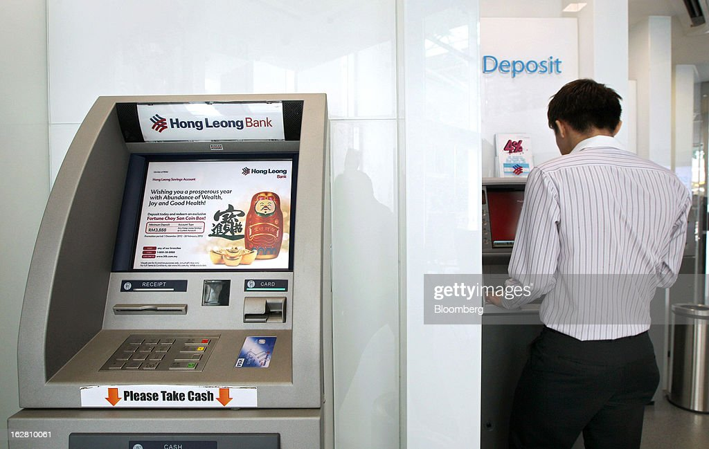 A customer uses a cash deposit machine inside one of Hong Leong Bank Bhd.'s Mach-branded branches in Petaling Jaya, Malaysia, on Wednesday, Feb. 27, 2013. Hong Leong Bank, the Malaysian lender controlled by billionaire Quek Leng Chan, plans to boost profit from overseas to as much as 20 percent of earnings as trade in Southeast Asia grows and emerging markets recover. Photographer: Goh Seng Chong/Bloomberg via Getty Images