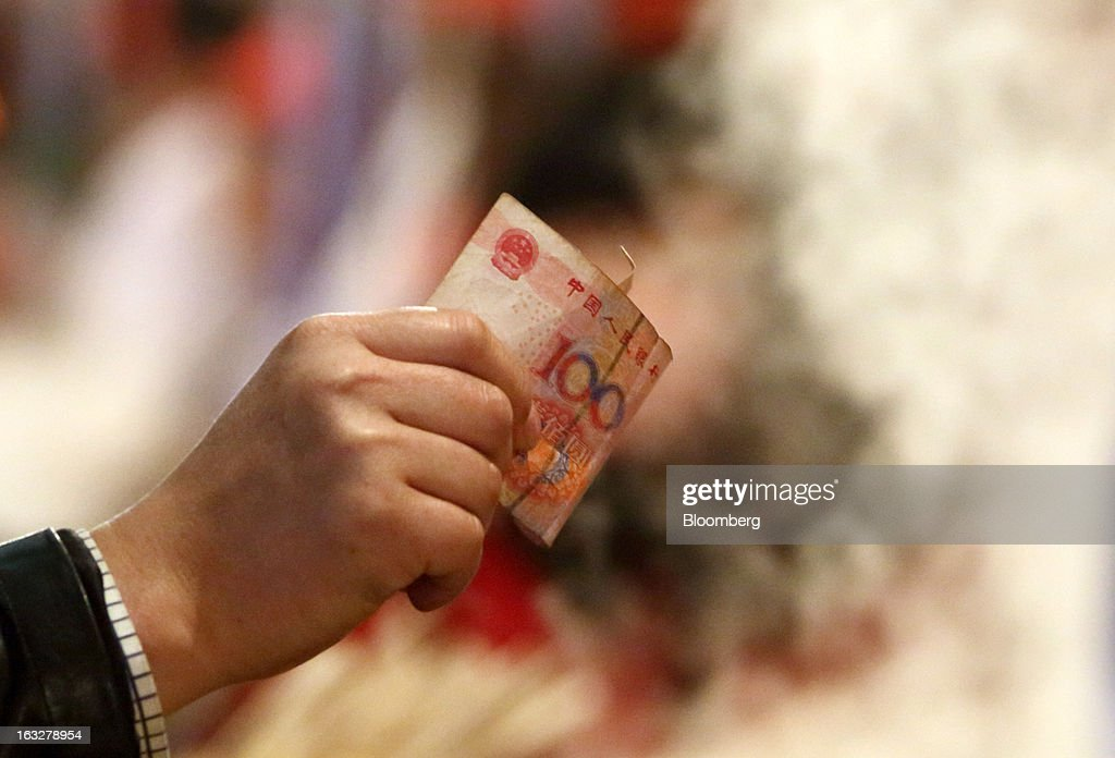 A customer uses a Chinese one-hundred yuan banknote as he shops at a stall in a market at night in Beijing, China, on Wednesday, March 6, 2013. China maintained its economic-growth target at 7.5 percent for 2013 while setting a lower inflation goal of 3.5 percent, setting up a challenge for new leaders to keep prices in check without harming expansion. Photographer: Tomohiro Ohsumi/Bloomberg via Getty Images
