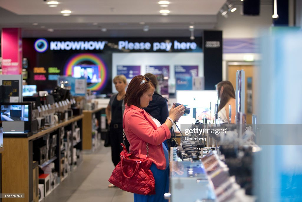 A customer uses a digital camera inside a Currys and PC World 2 in 1 store, operated by Dixons Retail Plc, at the Westfield Stratford City retail complex in London, U.K., on Thursday, Aug. 8, 2013. U.K. consumer confidence rose to the highest in more than three years as Britons' optimism about the economic outlook improved. Photographer: Simon Dawson/Bloomberg via Getty Images