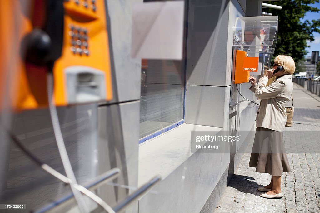 A customer uses a fixed line telephone in a booth outside the headquarters of Orange Polska, also known as Telekomunikacja Polska SA (TPSA), Poland's national telecommunications company, in Warsaw, Poland, on Wednesday, June 12, 2013. Cable providers are being drawn to Poland, the European Union's biggest eastern economy, because penetration levels are half that of neighboring Germany even as unemployment rises, according to a website presentation by the country's biggest TV network, Cyfrowy Polsat SA. Photographer: Bartek Sadowski/Bloomberg via Getty Images