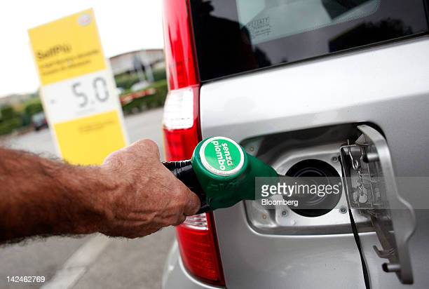 A customer uses a fuel pump to fill his automobile with unleaded petrol at an Esso gas station operated by Exxon Mobile Corp in Rome Italy on...