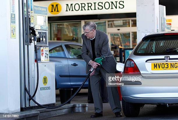 A customer uses a fuel pump to fill his vehicle with Unleaded petrol at a Morrison's gas station operated by William Morrison Supermarkets Plc in...