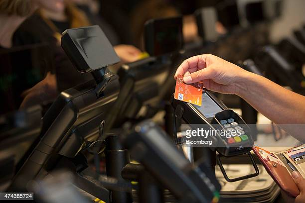 A customer uses a HSBC Holdings Plc Visa Inc credit card to make a contactless payment using a Verifone Systems Inc payment device at a restaurant in...