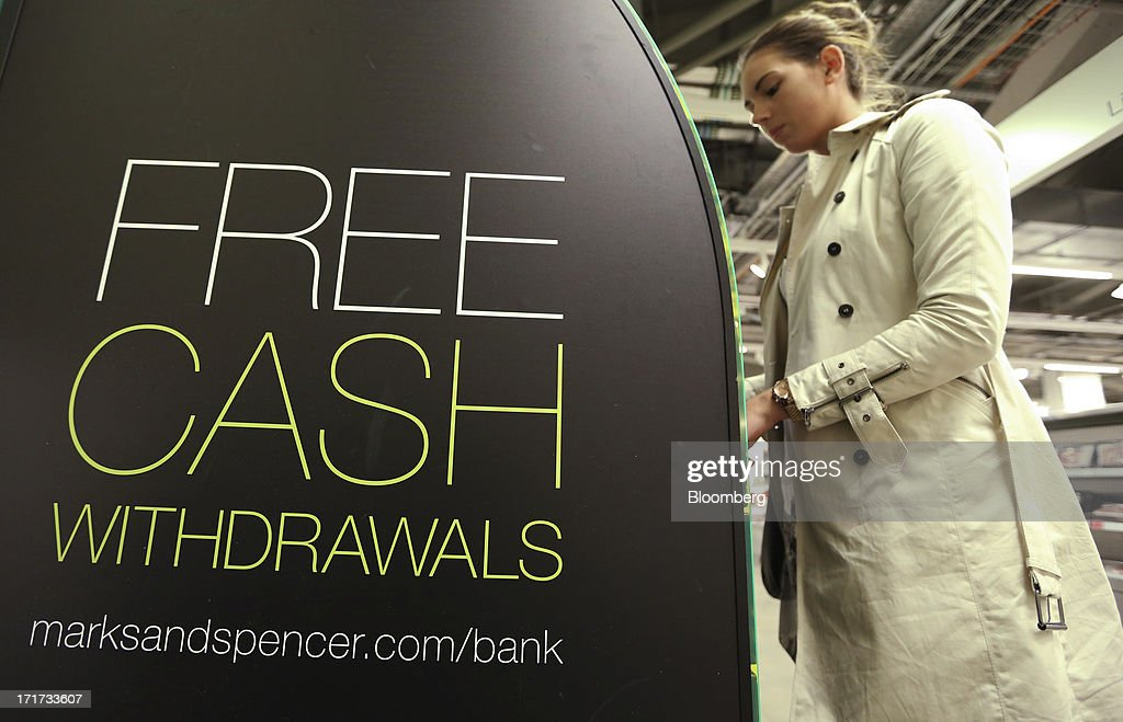 A customer uses a Marks & Spencer Group Plc (M&S) automated teller machine (ATM) inside a Marks & Spencer food hall in the Westfield Stratford City retail complex in London, U.K., on Thursday, June 27, 2013. U.K. retail sales rose more than economists forecast in May as consumers spent more online and food sales increased at their fastest pace for more than two years. Photographer: Chris Ratcliffe/Bloomberg via Getty Images