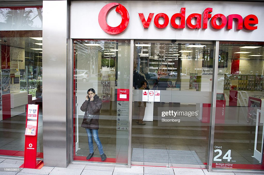 A customer uses a mobile handset in the window of a Vodafone Group Plc store in Barcelona, Spain, on Tuesday, Jan. 15, 2013. Vodafone Group Plc, the world's second largest mobile-phone company, plans to reduce the workforce at its Spanish unit as unemployment exceeding 25 percent in the recession-plagued country causes sales to drop. Photographer: David Ramos/Bloomberg via Getty Images