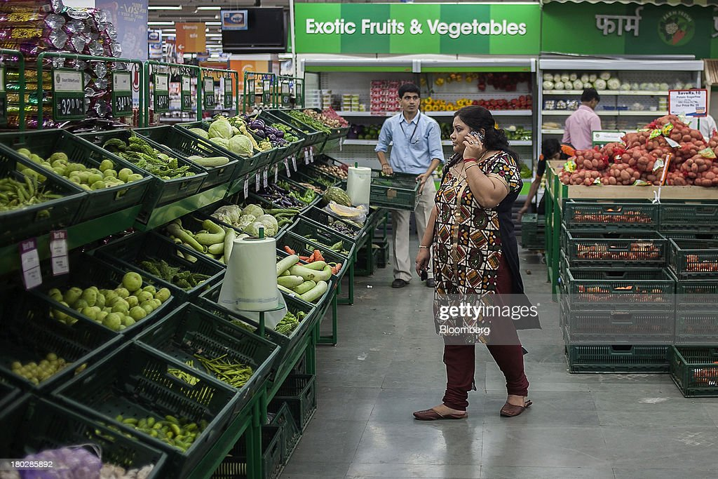 A customer uses a mobile phone as she browses produce in the vegetable section of the Big Bazaar Hypermarket store in Noida, India, on Monday, Sept. 9, 2013. Indias rupee fell, snapping the biggest four-day surge in 40 years, on concern slowing growth will deter inflows needed to reduce the current-account deficit. Photographer: Prashanth Vishwanathan/Bloomberg via Getty Images